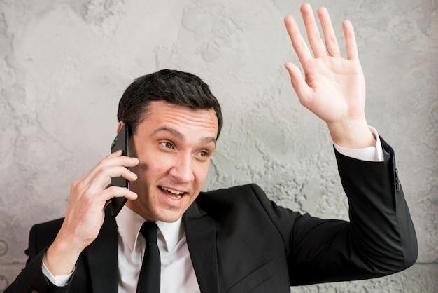 Geschäftsmann, der am telefon spricht und hand wellenartig bewegt Kostenlose Fotos