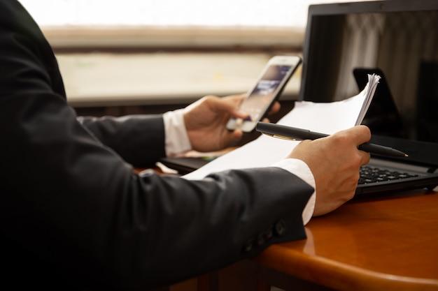 Geschäftsmann, der an dokumentenpapier unter verwendung des handys und des laptops arbeitet. Premium Fotos