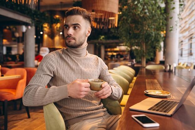Geschäftsmann, der an einem computer in einem café arbeitet Kostenlose Fotos