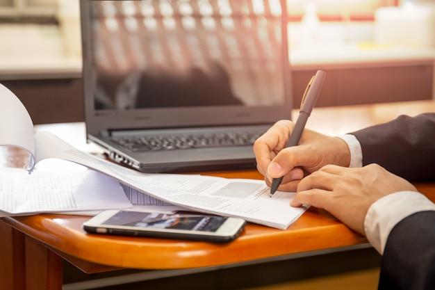 Geschäftsmann, der an laptop arbeitet und auf papiernotizbuch schreibt. Premium Fotos