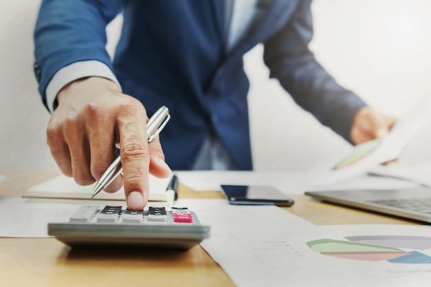 Geschäftsmann, der an schreibtisch arbeitet und taschenrechner im büro verwendet Premium Fotos