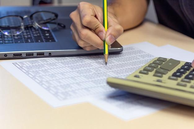 Geschäftsmann, der an schreibtischbüro mit einem taschenrechner- und bleistiftfinanzbericht arbeitet Premium Fotos