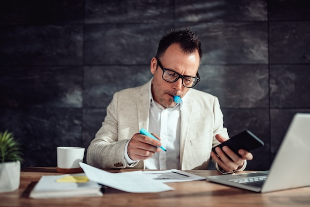 Geschäftsmann, der an seinem schreibtisch sitzt und text hervorhebt Premium Fotos