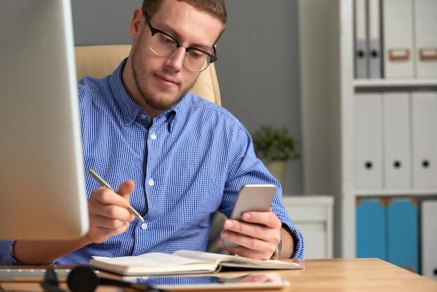 Geschäftsmann, der anzeigen-app am telefon und am tagebuch überprüft Kostenlose Fotos