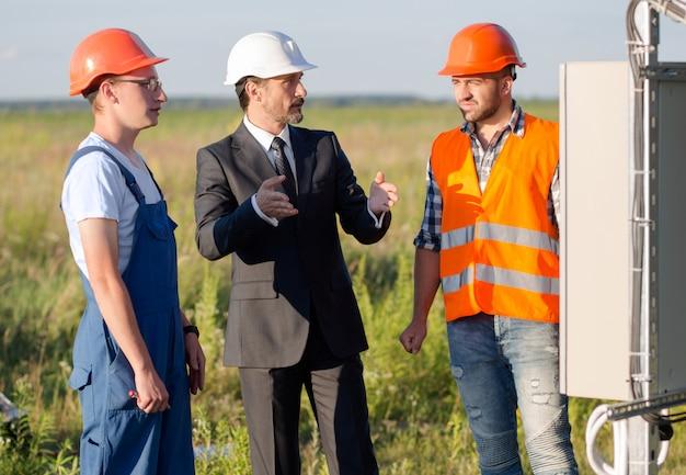 Geschäftsmann, der arbeitsprozeß von sonnenkollektoren angestellten erklärt. Premium Fotos