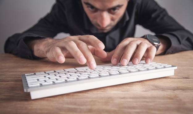 Geschäftsmann, der auf computertastatur tippt. Premium Fotos