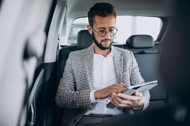 Geschäftsmann, der auf dem rücksitz eines autos mit tablette sitzt Kostenlose Fotos