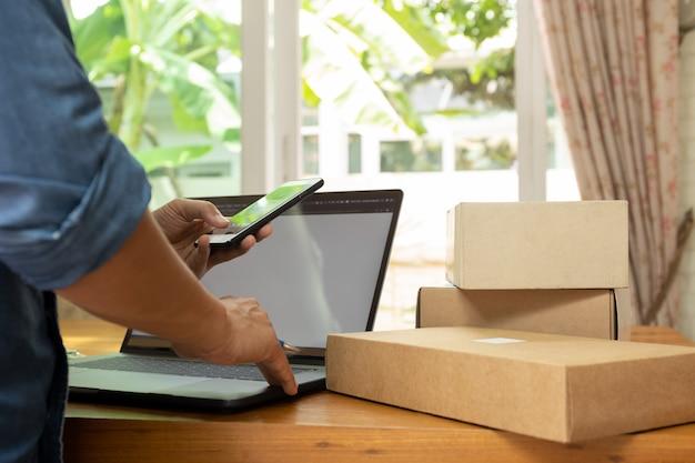 Geschäftsmann, der auf dem tisch elfenbein am handy mit paket und laptop überprüft. Premium Fotos