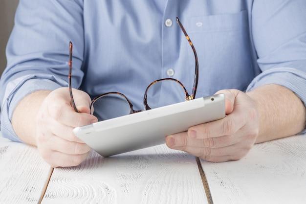 Geschäftsmann, der auf digitalem tablett im büro oder zu hause arbeitet Premium Fotos