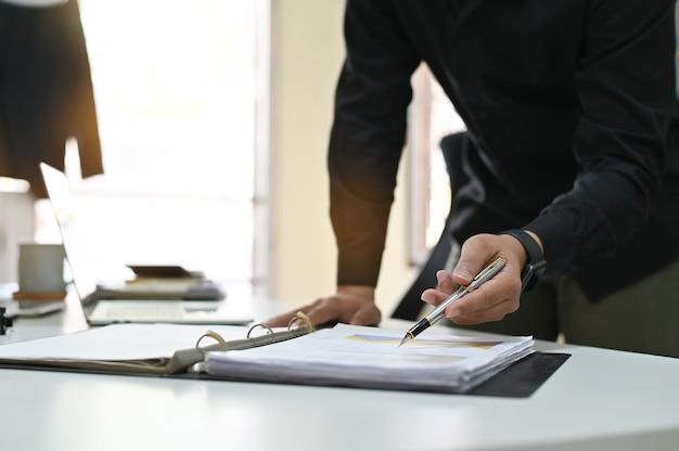 Geschäftsmann, der auf finanzdiagramm und -diagramm auf analysedokumentgebrauch zeigt, damit pläne qualität verbessern. Premium Fotos