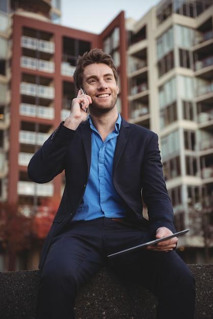 Geschäftsmann, der auf handy spricht und digitales tablett hält Kostenlose Fotos
