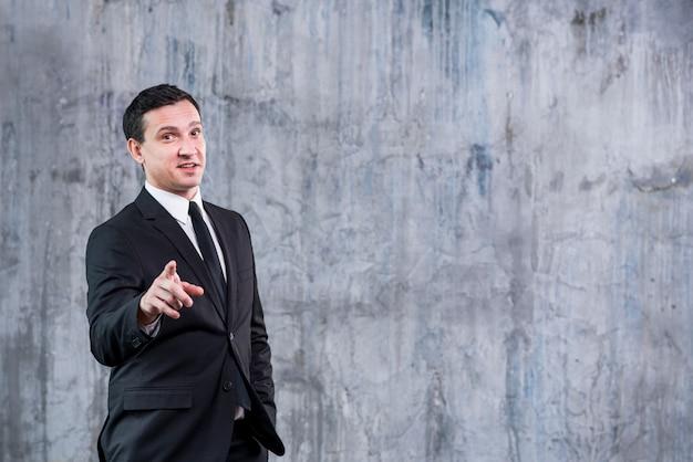 Geschäftsmann, der auf kamera gegen graue wand zeigt Kostenlose Fotos
