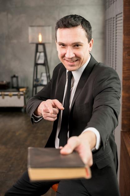 Geschäftsmann, der auf kamera zeigt und buch empfiehlt Kostenlose Fotos