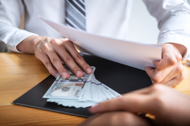 Geschäftsmann, der bestechungsgeld in den geschäftsleuten gibt, um erfolg den abkommenvertrag zu geben Premium Fotos