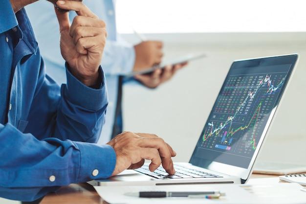 Geschäftsmann, der börsenbericht und finanzarmaturenbrett mit handelsnachrichten, mit schlüsselleistungsindikatoren analysiert. unternehmerteam, das im kreativen büro arbeitet Premium Fotos