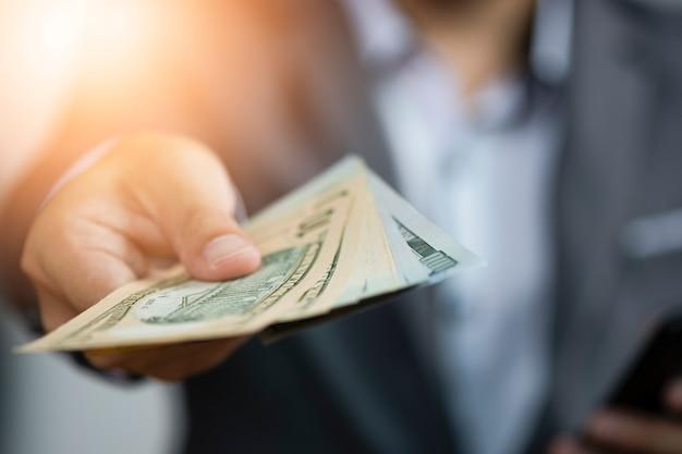 Geschäftsmann, der das geben von dollarbanknoten hält Premium Fotos