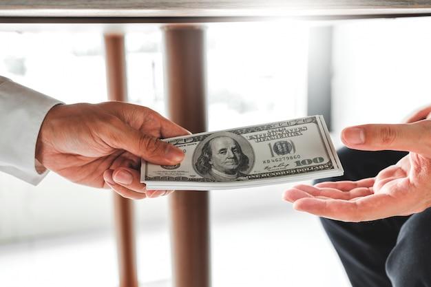 , geschäftsmann, der dem geschäftsführer dollarscheine gibt, um vertrag zu beschäftigen Premium Fotos
