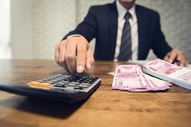 Geschäftsmann, der den umrechnungskurs für das geld der indischen rupie berechnet Premium Fotos