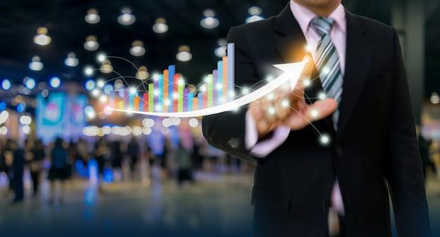 Geschäftsmann, der diagramm- und pfeilkonzept zeigt Premium Fotos