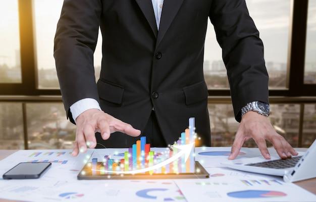 Geschäftsmann, der diagramme mit technologischen geräten analysiert Premium Fotos
