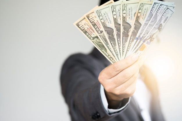 Geschäftsmann, der dollarbanknoten hält Premium Fotos