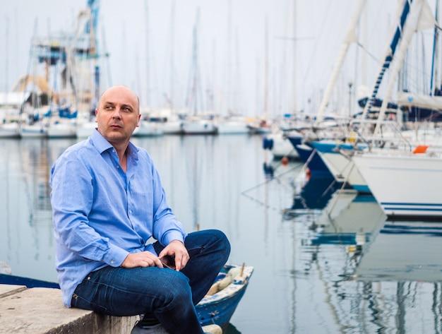 Geschäftsmann, der durch teure segelboote und yachten in einer küstenstadt sitzt Premium Fotos