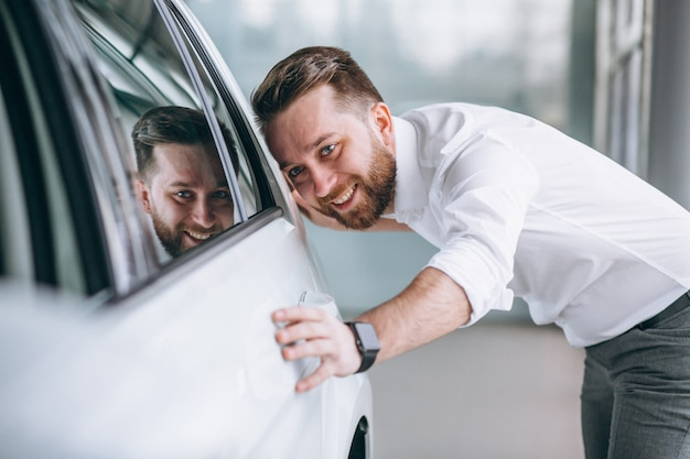 Geschäftsmann, der ein auto in einem ausstellungsraum kauft Kostenlose Fotos