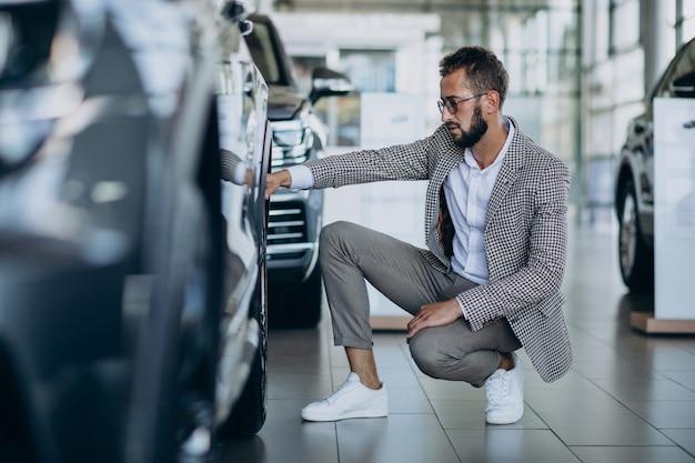 Geschäftsmann, der ein auto in einem autoausstellungsraum wählt Kostenlose Fotos