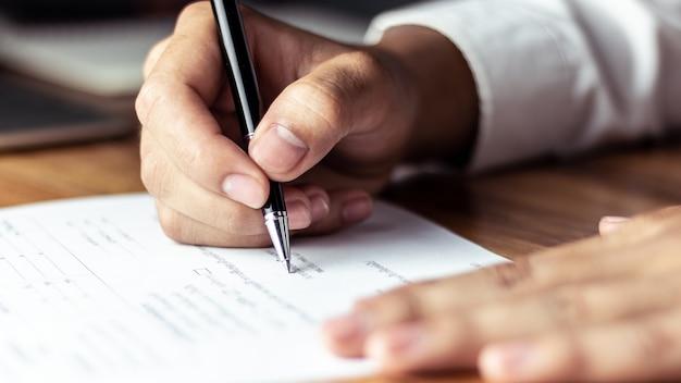 Geschäftsmann, der ein dokument im büro unterzeichnet Premium Fotos