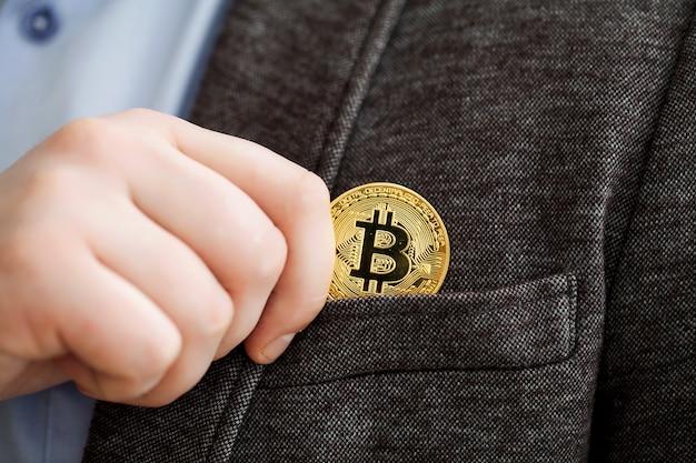 Geschäftsmann, der ein goldenes bitcoin in eine tasche entfernt oder legt Premium Fotos