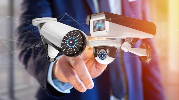 Geschäftsmann, der ein überwachungskamerasystem und eine network connection - wiedergabe 3d hält Premium Fotos