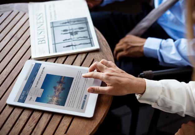 Geschäftsmann, der eine zeitung und eine geschäftsfrau liest nachrichten mit ihrem digitalen gerät liest Premium Fotos