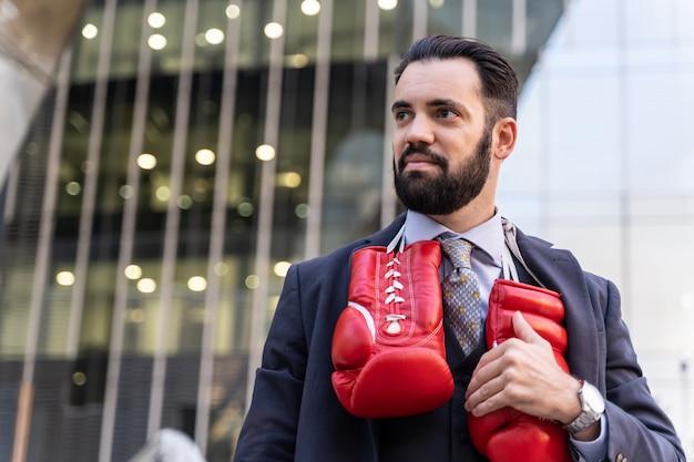 Geschäftsmann, der einen anzug trägt und die roten boxhandschuhe hängen von seinem hals berührt Kostenlose Fotos