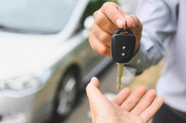 Geschäftsmann, der einen autoschlüssel gibt. neues autokonzept bekommen. Premium Fotos