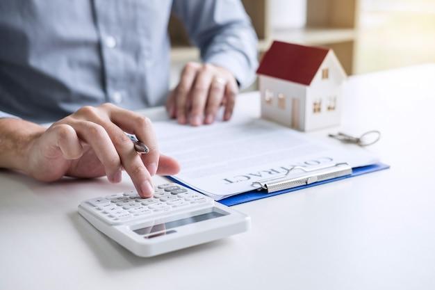 Geschäftsmann, der finanzen und berechnungskosten der immobilieninvestition tuend arbeitet, während zu unterschreiben zu unterzeichnen Premium Fotos