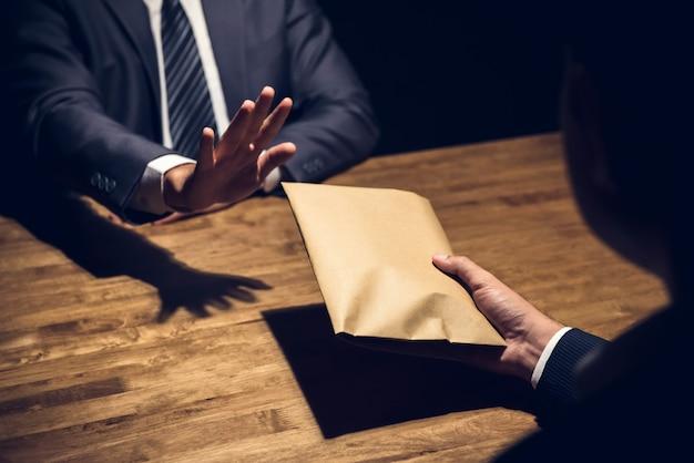 Geschäftsmann, der geld im umschlag zurückweist Premium Fotos