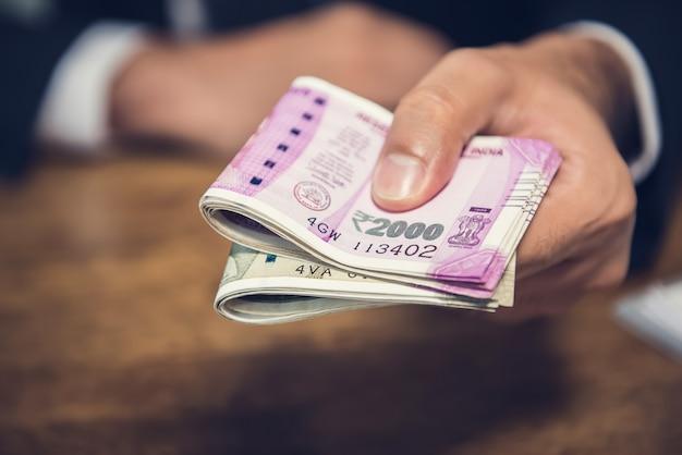 Geschäftsmann, der geld in form von indischen rupien für die erbrachten dienstleistungen gibt Premium Fotos
