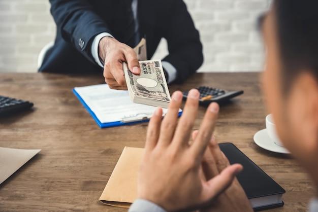 Geschäftsmann, der geld, japanische yen-währung, von seinem partner ablehnt Premium Fotos