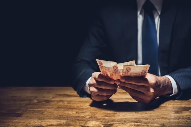 Geschäftsmann, der geld, währung des russischen rubels, im dunklen privaten raum zählt Premium Fotos