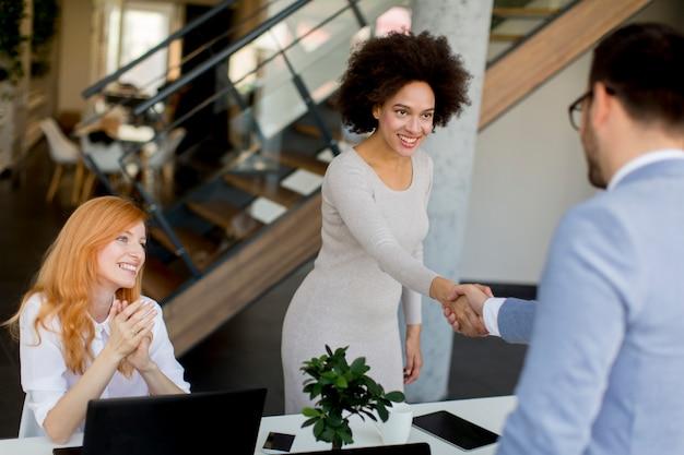 Geschäftsmann, der hände rüttelt, um ein abkommen mit seinem weiblichen partner zu versiegeln Premium Fotos