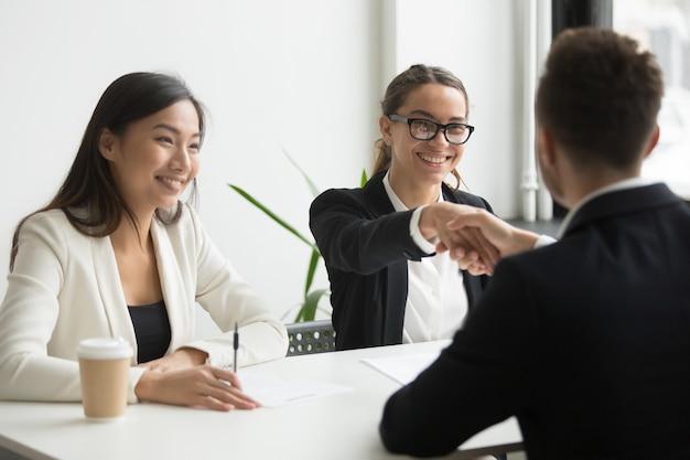 Geschäftsmann, der hand des weiblichen mitarbeiters während der firmasitzung rüttelt Kostenlose Fotos