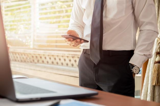 Geschäftsmann, der handy mit laptop auf hölzernem schreibtisch betrachtet. Premium Fotos