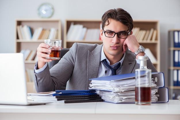 Geschäftsmann, der im büro trinkt Premium Fotos