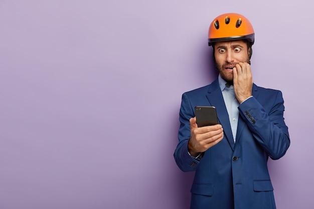 Geschäftsmann, der im noblen anzug und im roten helm im büro aufwirft Kostenlose Fotos