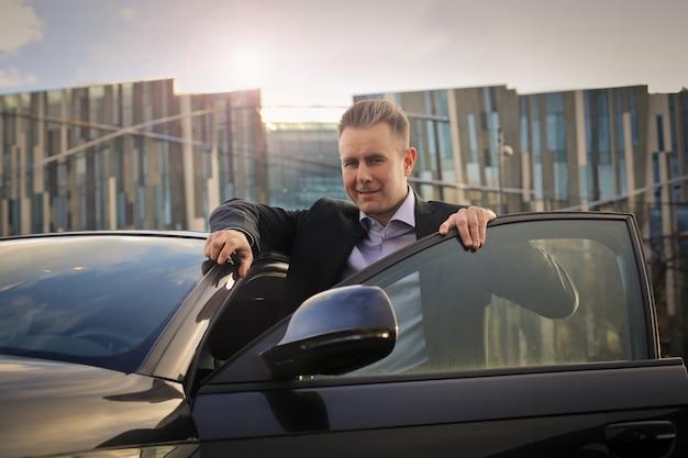 Geschäftsmann, der in sein auto einsteigt Premium Fotos