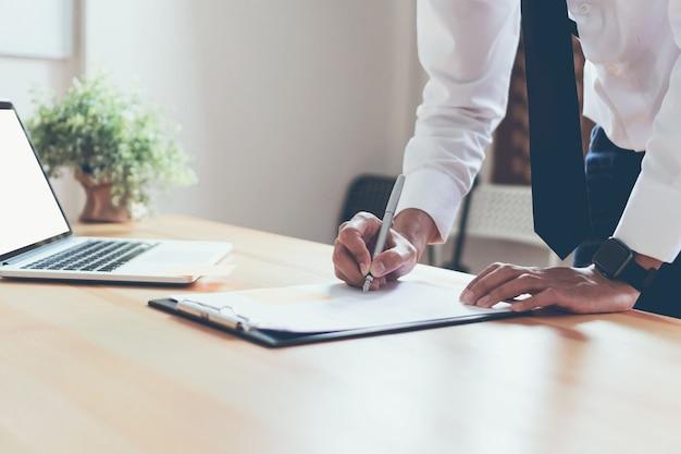 Geschäftsmann, der in seinem büro mit dokumenten arbeitet und die genauigkeit der informationen überprüfen. Premium Fotos