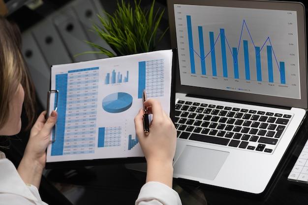 Geschäftsmann, der investitionsdiagramme mit laptop analysiert. buchhaltung Premium Fotos