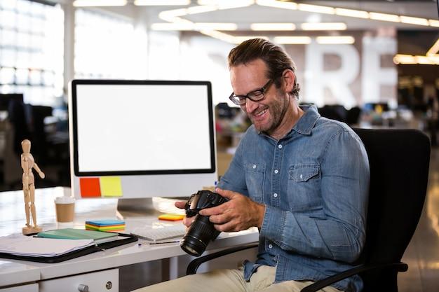 Geschäftsmann, der kamera beim sitzen am schreibtisch hält Premium Fotos
