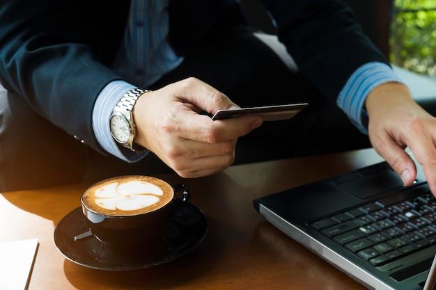 Geschäftsmann, der kreditkarte verwendet, um online einzelteile in der kaffeestube zu kaufen Kostenlose Fotos