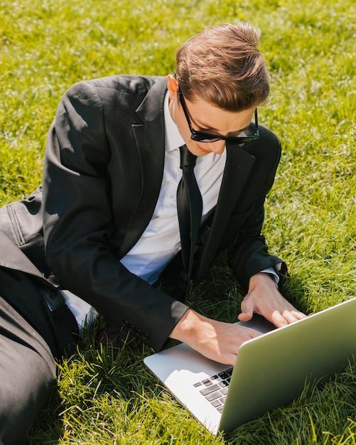 Geschäftsmann, der laptop auf grünem gras verwendet Kostenlose Fotos